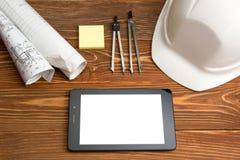 建筑师-建筑项目、计划、图纸卷和片剂个人计算机,笔,在空白纸的安全帽工作场所  免版税库存照片