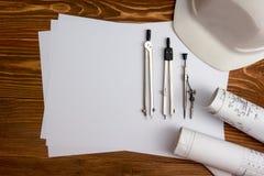建筑师-建筑项目、计划、图纸卷和片剂个人计算机,笔,在空白纸的安全帽工作场所  库存照片
