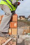 建筑泥工工作者测量缝的厚度在砖的 免版税库存图片