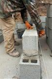 建筑泥工放置具体块有小铲的工作者瓦工基础墙壁户外 免版税库存图片