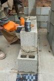 建筑泥工放置具体块有橡胶短槌的工作者瓦工基础墙壁户外 免版税库存照片