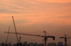 建筑用起重机剪影反对平衡淡色橙色天空的 免版税库存图片