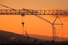 建筑用起重机和摩天大楼日落的 免版税库存照片