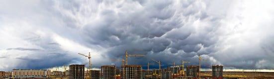建筑用起重机工业具体摩天大楼风暴雨天气天空全景 免版税库存照片