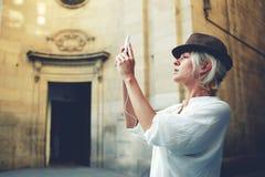 建筑纪念碑时髦的女性旅游制造的照片在期间,当游览在城市时 免版税库存照片