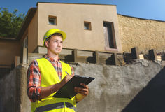 建筑背景的工头与一张剪贴板在他的手上 免版税库存图片