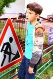 建筑边界的青春期前的英俊的男孩与警告信号 免版税库存照片