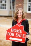 建筑:举行在家为销售标志的代理 免版税库存照片