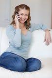 答复的长沙发电话坐的妇女 库存照片