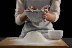 筛从碗的妇女面粉在木板 图库摄影