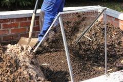 筛堆肥的地球 免版税库存照片