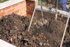 筛堆肥的地球 免版税图库摄影