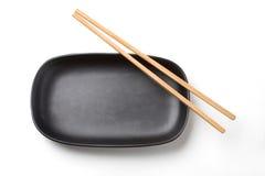 筷子和黑盘 免版税库存图片