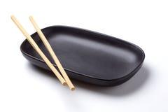 筷子和黑盘 免版税库存照片
