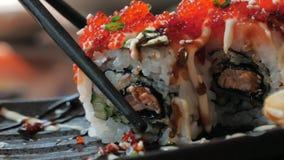 筷子特写镜头在餐馆拿着寿司卷一块板材 烹调日本传统 股票视频