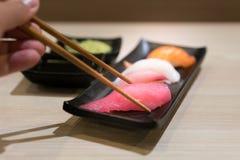 筷子用日本未加工的金枪鱼寿司和新鲜的混合寿司持续  库存图片