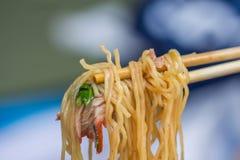 筷子用面条用在调味汁的烤红色猪肉 免版税库存照片
