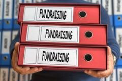 筹款的概念词 3d概念被回报的文件夹照片 圆环包扎工具 库存照片