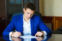 签一个合同的商人在大办公室 免版税库存照片