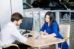 签一个合同的女商人在售车行办公室 库存照片