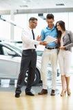 签一个合同的年轻夫妇在汽车陈列室里 免版税库存图片
