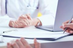 签医疗合同的患者 女性医生解释如何填装医疗形式 库存照片