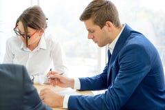 签合同的商人在表附近在现代办公室 企业合作概念 免版税库存图片