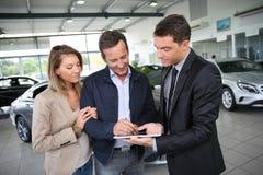 签在片剂的夫妇一个购买契约 免版税库存图片
