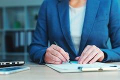 签字企业的协议,女实业家手写署名 免版税图库摄影