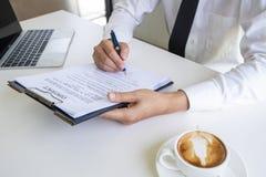 签署与笔的商人的手合同文件在书桌上 免版税库存图片