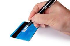 签署他的信用卡的后面商人的手 免版税库存图片
