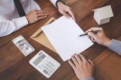 签署合同买进卖出房子,人标志的事务由于房屋贷款的一个家庭保险单,分析关于家的保险代理公司 免版税库存图片