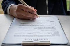 签署合同文件的商人的手 免版税库存图片