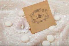 签署在白色发光的织品的爱与一朵白色紫罗兰 库存照片