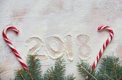 签署在面粉的新年好2018年在木桌上装饰用红色糖果和圣诞节三个分支 顶视图 图库摄影