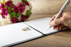 签署婚姻记数器的人 库存图片