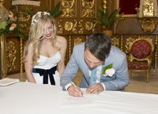 签署寄存器的新娘和新郎在教会里 图库摄影