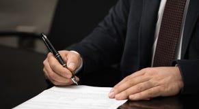 签署或写文件的商人的手在白皮书一张使用nibbed钢笔 图库摄影