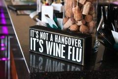 签署说它不是宿酒它的酒通气管坐酒吧大理石工作台面与后边的瓶子的黄柏 图库摄影