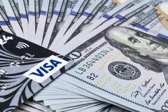 签证与堆的信用卡一百元钞票 堆现金金钱在一百美元钞票相信塑料银行卡 库存照片