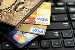 签证和万事达卡信用卡在钱包里在keyboar的笔记本 免版税库存图片