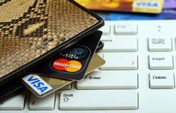 签证和万事达卡信用卡在钱包里在keyboar的笔记本 图库摄影