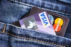 签证和万事达卡在蓝色牛仔裤的信用卡装在口袋里 库存照片