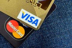 签证和万事达卡在蓝色牛仔裤的信用卡 库存图片