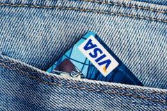 签证在蓝色牛仔布牛仔裤的转账卡装在口袋里。 免版税库存图片