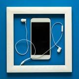 简单派 在木制框架的杰作 与耳机的Smartphone 技术当艺术概念 免版税图库摄影