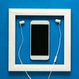简单派 在木制框架的杰作 与耳机的Smartphone 技术当艺术概念 免版税库存图片