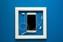 简单派 在木制框架的杰作 与耳机的Smartphone 技术当艺术概念 库存图片