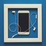 简单派 在木制框架的杰作 与耳机的Smartphone 顶视图 平的位置 技术当艺术概念 免版税库存图片