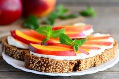 简单的三明治用乳脂干酪、新鲜的油桃和薄菏在板材和在葡萄酒木桌上 库存照片